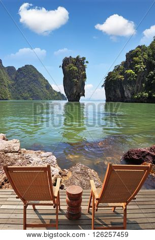 The comfortable place to enjoy the beauty of the landscape. Two wooden chairs - on a wooden platform.  The island in the shape of a green vase in the sea bay with pure emerald water