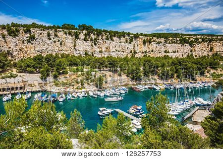 The picturesque fjord with turquoise water at coast of the Mediterranean Sea. National park of Calanques in Provence, between Marseille and Kassis.  Graceful sailing yachts in the deep sea gulf
