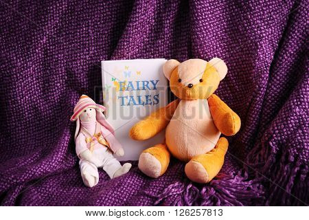 Rag toys with fairy tales book on  bedspread. Childhood concept