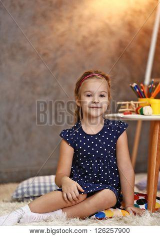 Beautiful small girl sitting on carpet