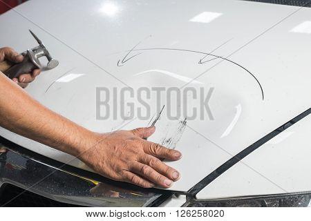 Auto body repair series: Mechanic checking damaged on white car bonnet