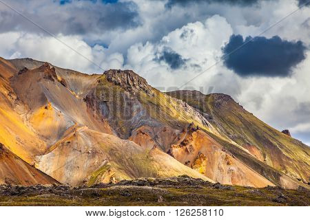 Summer volcanic tundra.  Bright and multi-colored rhyolite mountains - yellow, orange, green and blue. Travel to Iceland in July