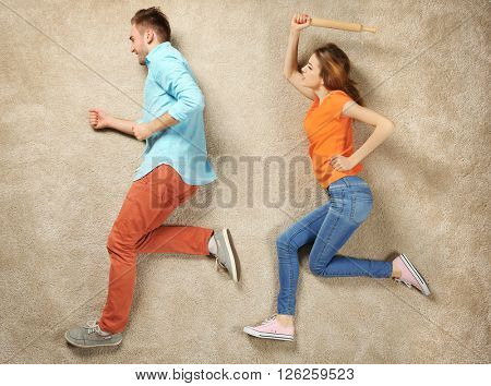 Scene simulation, woman catching up with man and trying to beat him with a rolling pin