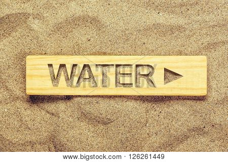 Water direction sign in dry desert sand guide signpost for thirsty man.