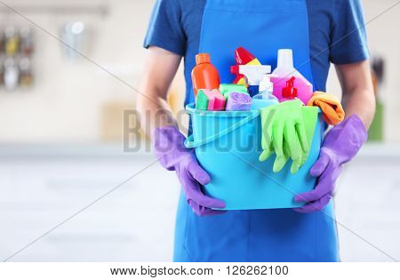 Man holding plastic bucket with brushes, gloves and detergents in the kitchen