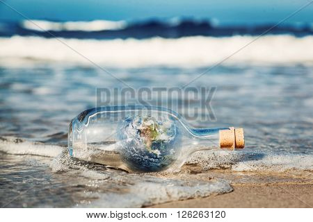 Earth in the bottle coming with wave from ocean. Concept of environment, nature care, save clean world message. Elements of this image furnished by NASA