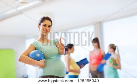 pregnancy, sport, fitness, people and healthy lifestyle concept - happy pregnant woman with ball in gym showing thumbs up
