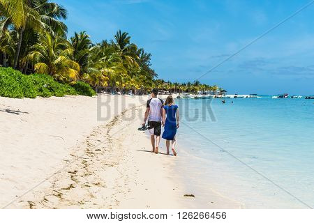 Le Morne Mauritius - December 7 2015: A couple enjoying a walk on the Beach at Le Morne Brabant one of the finest beaches in Mauritius and the site of many hotels and tourism facilities.