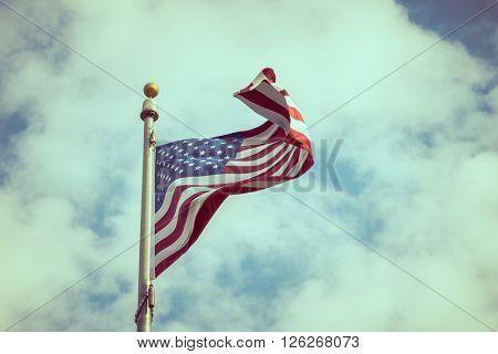 American flag on blue sky ( Filtered image processed vintage effect. )