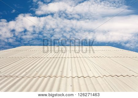 White asbestos slate roof against blue sky