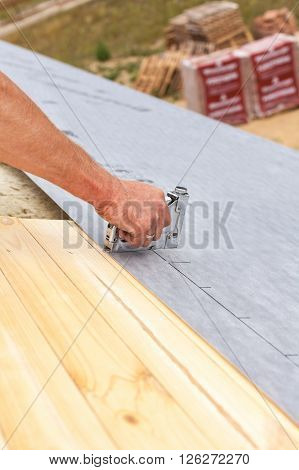 Roofer nails lining using construction stapler. Roof under construction