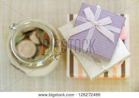 Striped, silver and purple gift boxes stacked together beside glass jar filled with coins on textured background. Selective focus to emphasize. Concept of saving for present or special occasion.