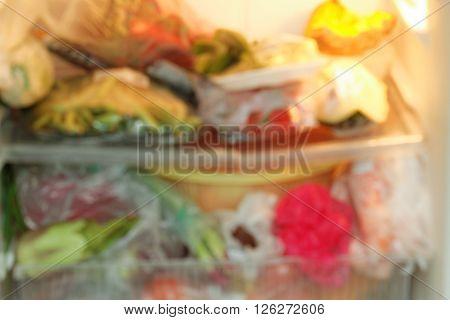 Inside of unkempt refrigerator. Blurred. Showing unorganized refrigeraor.