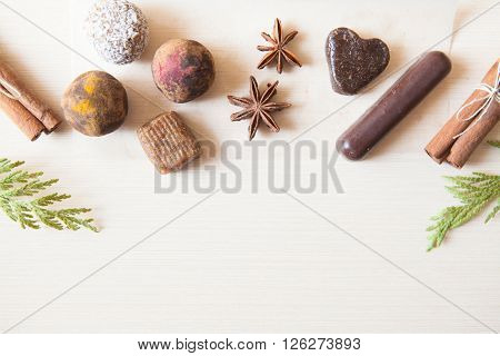 Cuisine background. Six raw candies made of date fruit nuts hibiscus curry cocoa coconut decorated with cinnamon sticks cardamom thuja branches on light wooden background indoors. Healthy and raw sweet-shop design content.