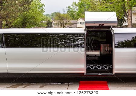 White luxury limousine with open up door and red carpet leading to.