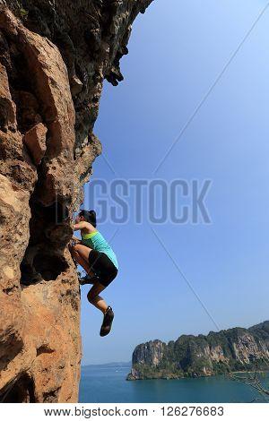 free solo woman rock climber climbing at seaside mountain rock wall