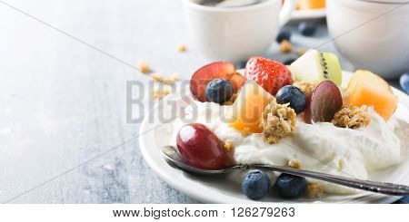 Breakfast, quark with granola, fruits and berries on light wooden background. Healthy food concept with copy space for text.