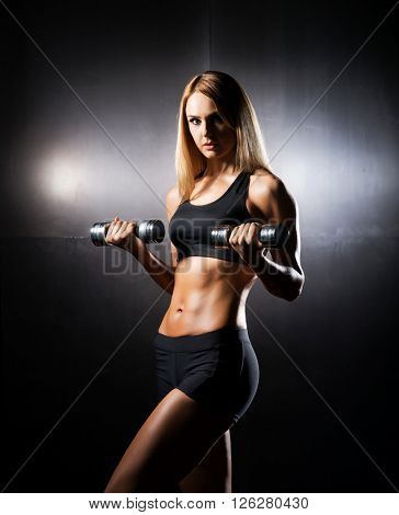 Athletic, fit and sporty girl having a dumbbell training in the gym.