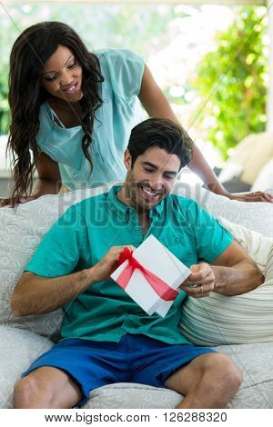 Woman watching a man while unwrapping a gift at home