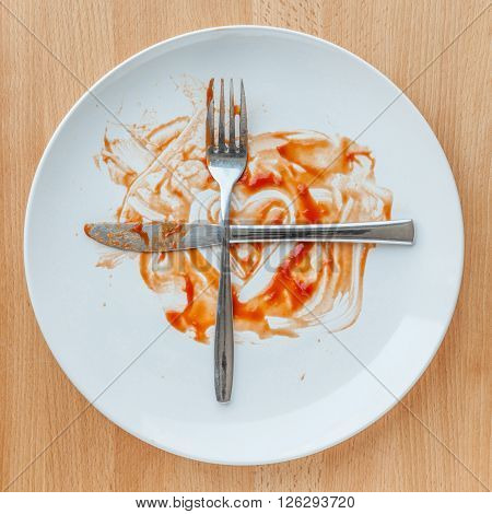 Knife and fork crossed in finish plate and heart shape ketchup concept of tasty and meaning ready for second plate.