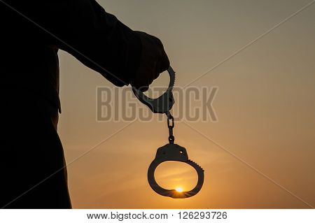 Business Man Holding Handcuffs After Releasing Over Sunset Background. Freedom And Burden-free Conce