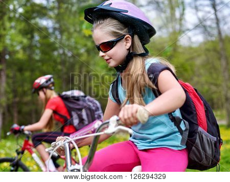 Bikes cycling girls with rucksack cycling in summer park.