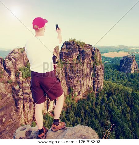 Short Hair Man On Cliff Of Rock And Takes Photo By Smart Phone Of Landscape Bellow. Sunny Day In Roc