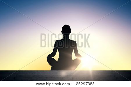 people, health, wellness and meditation concept - woman meditating in yoga lotus pose on stairs over sun light background