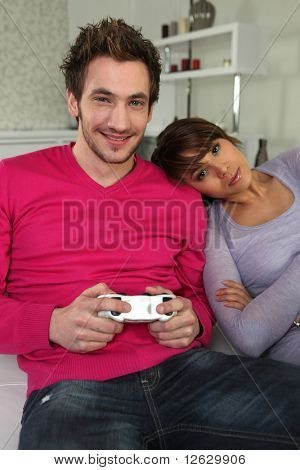 Woman sitting near a man playing video game