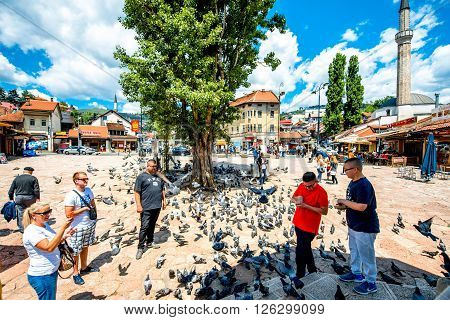 SARAJEVO, BOSNIA - HERZOGOVINA - CIRCA JUNE 2015: Crowded old market squire with pigeons on the north bank of the river Miljacka in the municipality of Stari Grad in Sarajevo.