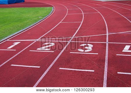 Red running racetrack on the outdoor stadium, numbers