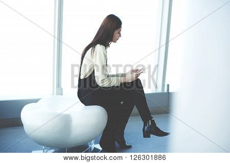 Japanese woman professional employee is reading information on web page via cell phonewhile is sitting in office interior. Young female asian student is checking e-mail via mobile phone in university