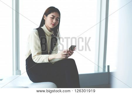 Confident Japanese female is making on-line purchase via mobile phone while is waiting her plane in departure airport hall. Young businesswoman reading text message on cell phone during break at job