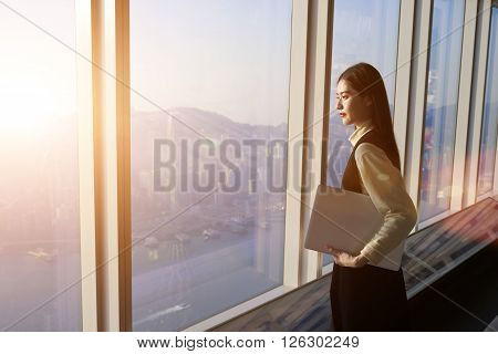 Successful female office worker with net-book is standing in skyscraper interior against big window with city view on background. Proud asian woman architect looking satisfied with completed project