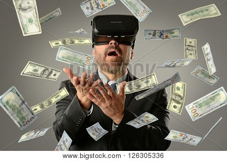 MAture businessman using virtual reality glasses getting money into hands