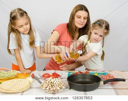 Two Little Girls At The Kitchen Table With Enthusiasm To Help My Mother To Pour Vegetable Oil In A F