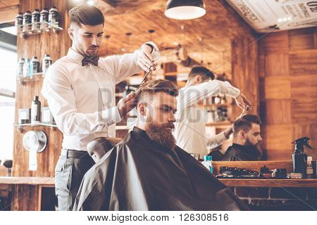 Everything should be perfect. Side view of young bearded man getting haircut by hairdresser while sitting in chair at barbershop