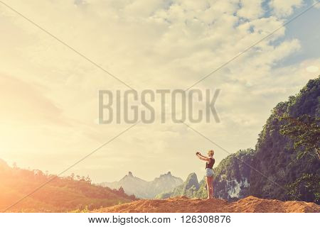 Woman traveler is taking photo with cell telephone camera of a fascinating jungle landscape in sunset. Young female tourist is shooting video on mobile phone while standing against subtropical forest