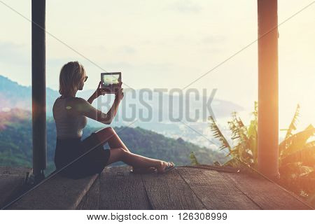 Woman is shooting video on touch pad of beautiful view during her long awaited summer vacation in Thailand. Female wanderer is making photo with digital tablet camera of an amazing jungle landscape