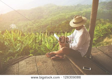 Man traveler is reading electronic book on portable touch pad while is relaxing in the fresh air during trip in Asia.Male freelancer is working on digital tablet while is sitting against jungle view