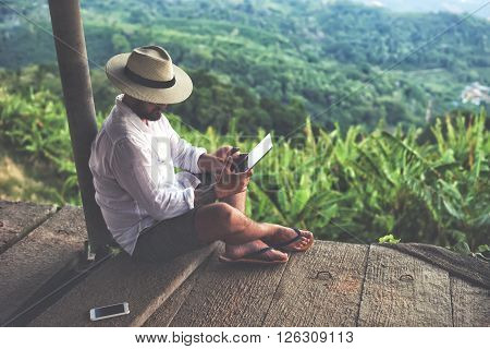Man traveler is using digital tablet while is sitting against beautiful Asian scenery during summer journey. Male wanderer is holding touch pad while is relaxing outdoors during his trip in Thailand