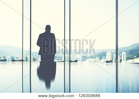 Silhouette of a man jurist is resting after hard work day while is standing in private office near window with view of business center in Hong Kong.Copy space background for your advertising content