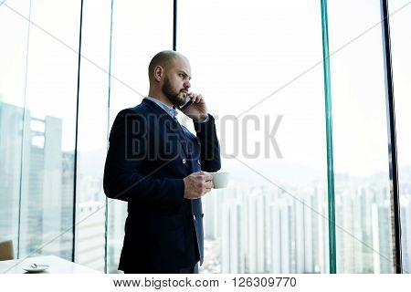 Young man successful entrepreneur in suit is phoning via his cell telephone during coffee break in work day while is standing near office window with view of business district with tall skyscrapers