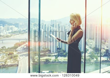 Young successful female boss is talking on cell telephone with customer and read information on website via digital tablet while is standing in modern office interior near window with cityscape view