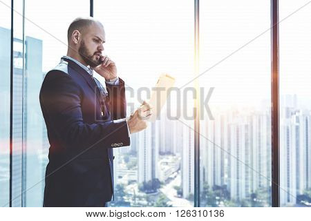 Young man proud CEO is analyzing activity of the company via digital tablet and talking with financial manager during his business trip in China while is standing near office window with copy space