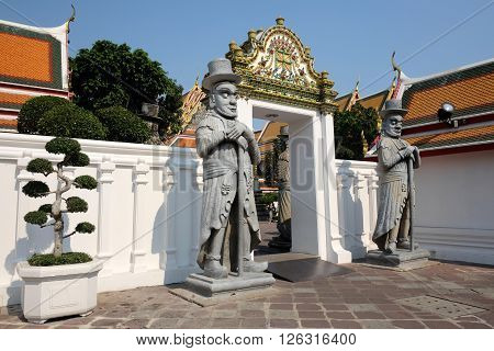 TRANSITION GATE WITH STATUE Temple transition gate decorate with relief art and two stone warrior statues.