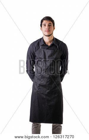 Young chef or waiter posing, wearing black apron and shirt isolated on white background