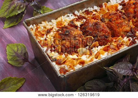 Baking tin filled by roasted meatballs and rice