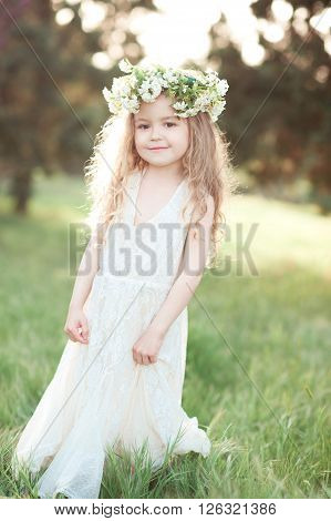 Cute kid girl 3-4 year old wearing stylish white dress and floral wreath outdoors. Childhood. Wedding day.