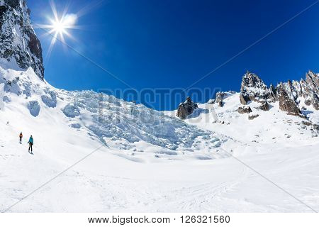 CHAMONIX, FRANCE - MARCH 19, 2016: a group of skiers go downhill in front of the giant icefall of Valle Blanche. Mont Blanc, Chamonix, France, Europe.